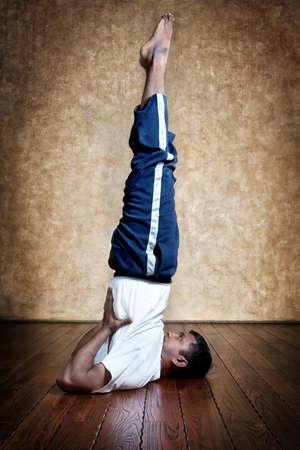 inverted: Handsome Indian man in white shirt doing salamba sarvangasana, shoulder stand inverted pose indoors on wooden floor at grunge background