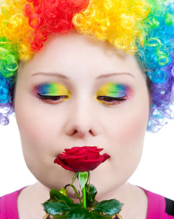 Beautiful woman in rainbow clown wig and creative rainbow make-up smelling red rose at white background photo