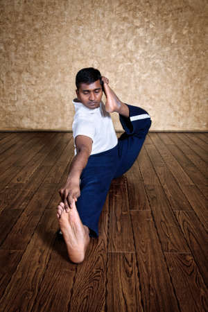 dhanurasana: Handsome Indian man in white shirt doing akarna dhanurasana, archer pose front side indoors on wooden floor at grunge background