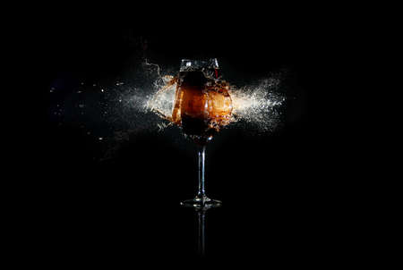 breaking: Glass with brown liquid exploded by bullet with many splashes around at the black background