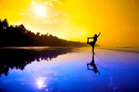 bailarines silueta: Silueta de una hermosa joven haciendo yoga natarajasana bailarín pose en la playa al atardecer en colores púrpuras y naranjas