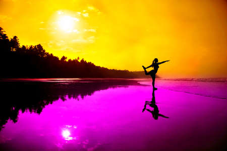 Silhouette of a beautiful young girl doing yoga natarajasana dancer pose on the beach at the sunset in magenta and orange colors Stock Photo - 9604104