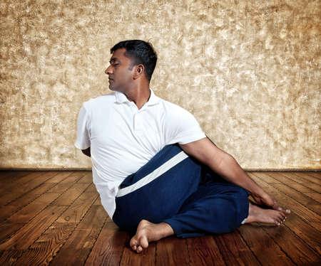 Handsome Indian man in white shirt doing ardha matsiendrasana twist pose indoors on wooden floor at grunge background photo