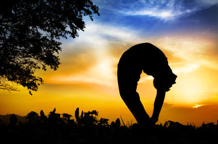 Man silhouette doing tiriang mukhottanasana backward bending pose with tree nearby outdoors at sunset background photo