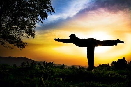 Man silhouet doen virabhadrasana III warior pose met boom in de buurt van buiten bij zonsondergang achtergrond