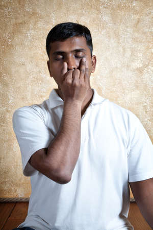 nostril: Handsome Indian man in white shirt doing nadi suddhi pranayama with Vishnu mudra gesture close-up indoors on wooden floor at grunge background