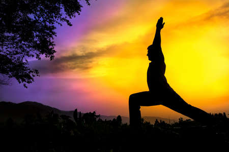 Man silhouette doing virabhadrasana I warrior pose with tree nearby outdoors at sunset background