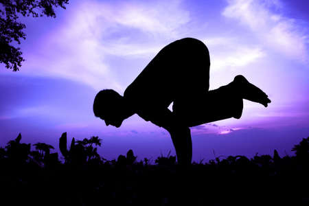 Man silhouette doing bakasana, crane pose with tree nearby outdoors at sun rise background Stock Photo - 9726855