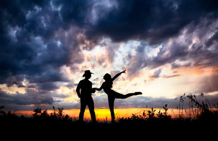 Young couple silhouette outdoors at sunset dramatic sky background. Man in cowboy hat and woman dancing near by photo