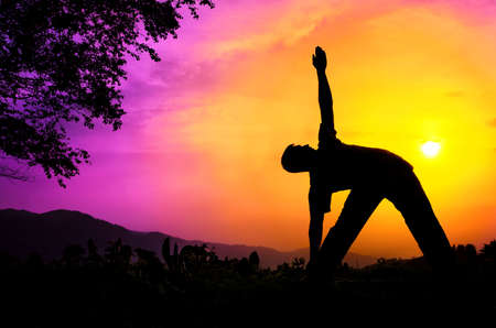 Man silhouette doing utthita trikonasana triangle pose with tree nearby outdoors at sunset background photo