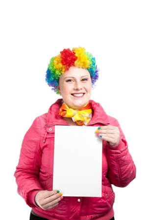 Beautiful woman in rainbow clown wig with freckles and creative rainbow make-up smiling and holding white blank banner in her arms at white background photo