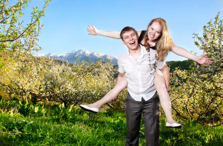 bloomy: Beautiful couple smiling and having fun with each other around bloomy apple trees at mountain background
