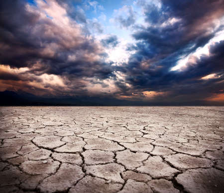 natural disaster: drought earth and storm dramatic sky at background