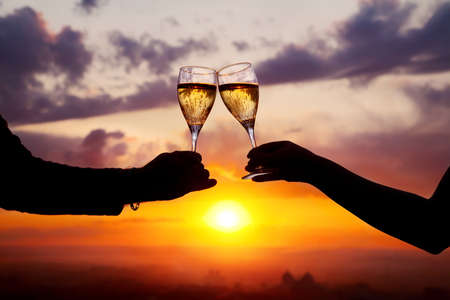 Man and woman clanging wine glasses with champagne at sunset dramatic sky background Stock Photo