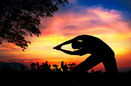 Man silhouette doing parighasana beam pose with tree nearby outdoors at sunset background photo