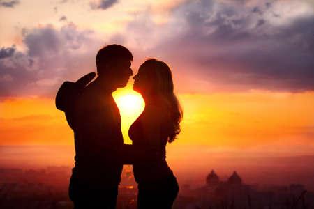 siluetas de enamorados: Joven pareja silueta abrazos y besos al aire libre en el fondo del atardecer. Sun entre ellos. Hombre con sombrero de vaquero en su espalda