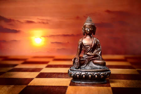 textural: Bronze Buddha sitting in padmasana on textural chess desk floor at sunset background