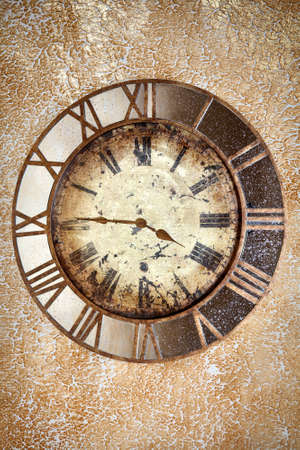 past midnight: Ancient scratched vintage clock with roman numbers on the grunge wall background