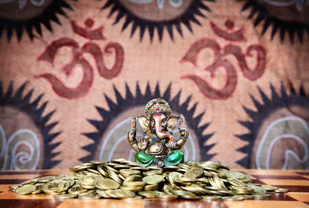 indian money: Little statue of ganesh in green trousers sitting on the heap of golden coins on chess desk at om signs background