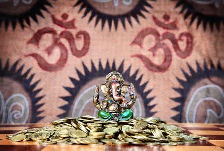 ganesh: Pequeña estatua de ganesh en pantalones verdes sentado en el montón de monedas de oro sobre mesa de ajedrez en fondo de signos de om Foto de archivo