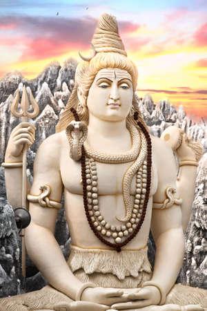 cobra: Gran estatua de Shiva sentado en lotus con tridente en su mano y cobra alrededor de su cuello en fondo puesta del sol. Bangalore, India Foto de archivo