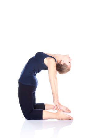 Beautiful Caucasian woman in blue Capri and top doing ushtrasana, camel pose at white background. Free space for text photo
