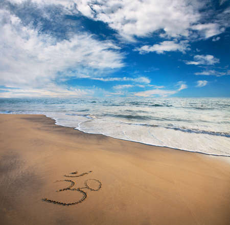 Om symbol on the sand at the beach near the ocean. Blue sky with clouds