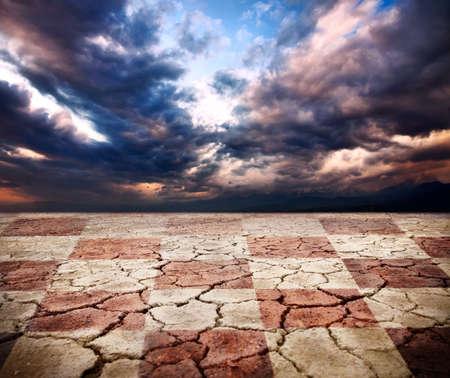 sequias: Tierra de sequ�a con textura de escritorio de ajedrez en fondo de cielo dram�tico de tormenta