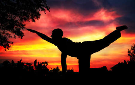 Man silhouette doing parshva marjariasana cat pose with tree nearby outdoors at red sunset background Stock Photo - 9825803