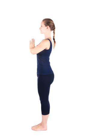 Beautiful Caucasian woman in blue Capri and top doing first step of surya namaskar, sun salutation Exercise at white background photo