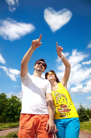 Young positive couple in sunglasses pointing at the heart from clouds at blue sky photo