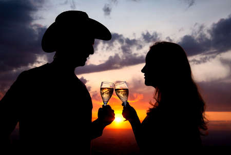 Silhouettes of Man in cowboy hat and woman clinging glasses of champagne at sunset dramatic sky background Stock Photo - 9972378