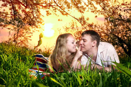 Young beautiful couple lying on blanket around green grass and woman touching mouth of her boyfriend. Sunset sky background photo