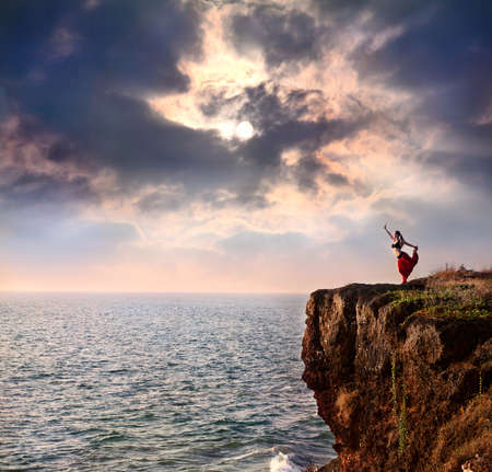 Beautiful woman doing natarajasana dancer yoga pose on the cliff near the ocean with dramatic sky at background in India