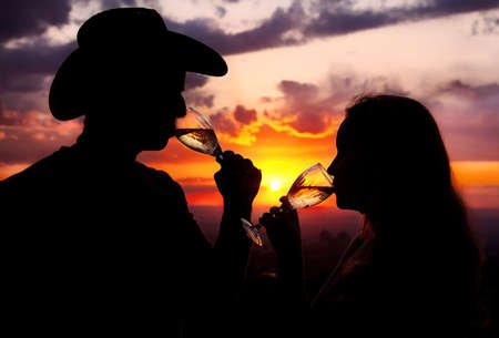 Silhouettes of Man in cowboy hat and woman drinking champagne from wine glasses at sunset dramatic sky background photo