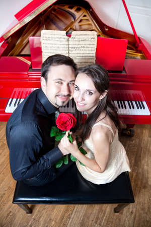 Young beautiful couple sitting on the chair near the red grand piano. Holding red rose, smiling and looking at camera Stock Photo - 10070596