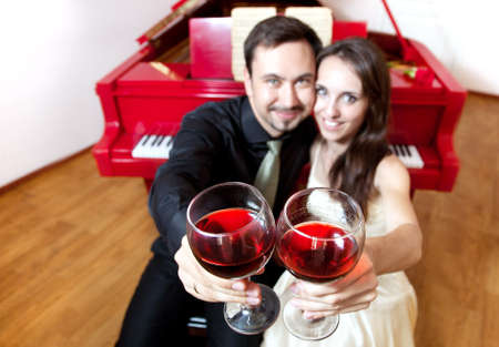 clang: Man and woman clanging wine glasses with red liquid near by red grand piano