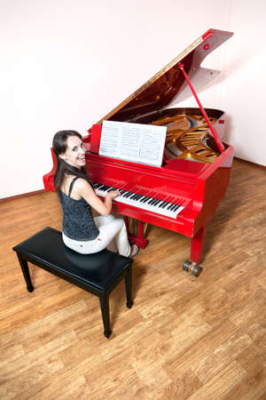 Happy Beautiful Caucasian woman playing the red grand piano, smiling and looking at camera photo