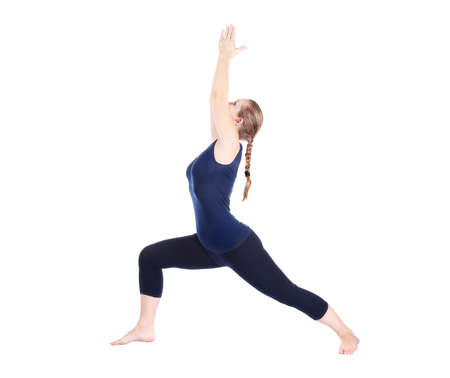Beautiful Caucasian woman in blue Capri and top doing virabhadrasana I, warrior pose at white background. Free space for text photo