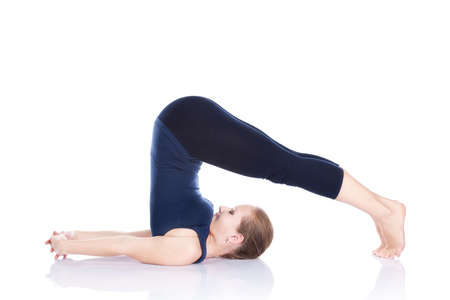 Beautiful Caucasian woman in blue Capri and top doing halasana, plough pose at white background. Free space for text photo