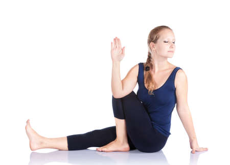 twist: Beautiful Caucasian woman in blue Capri and top doing marichiasana III, twist pose at white background. Free space for text