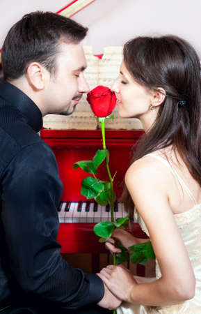 Young beautiful couple near the red grand piano Holding red rose and smelling it with eyes closed  Stock Photo - 10070598
