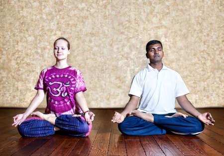 dhyana: Due persone: uomo indiano e caucasica donna nel luminoso viola panno indiano facendo meditazione yoga in postura lotus padmasana con dhyana mudra a background grunge con pavimento in legno