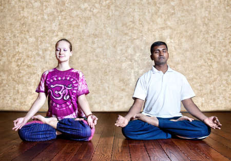Two persons: Indian man and Caucasian woman in bright purple Indian cloth doing yoga meditation in padmasana lotus posture with dhyana mudra at the grunge background with wooden floor photo