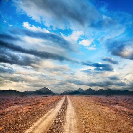 Camino a la montaña a través del desierto en el cielo con nubes Foto de archivo
