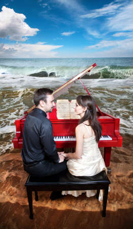 Young couple sitting in front of the red grand piano and looking at each other. Piano standing on the beach near the ocean with waves and blue sky at the background  photo
