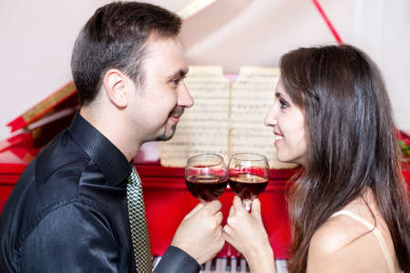 Man and woman clanging wine glasses with red liquid and looking at each other near by red grand piano  Stock Photo - 10373419
