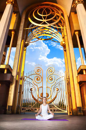 Beautiful Caucasian woman in white cloth doing meditation in ardha padmasana, half lotus pose. Huge golden gate with columns and blue sky with big cloud at background