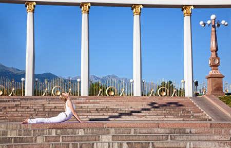bhujangasana: Beautiful Caucasian woman in white cloth doing bhujangasana cobra pose, sixth step of surya namaskar sun salutation Exercise. Woman laying in prone position on stone stairs and columns, mountains, blue sky at background Stock Photo