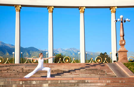 virabhadrasana: Beautiful Caucasian woman in white cloth doing virabhadrasana II, warrior pose. Woman standing on the stone stairs. Columns, mountains, blue sky at background